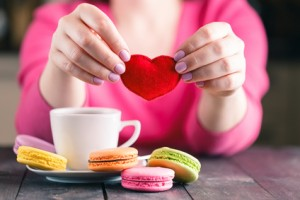 Woman drink coffee and holding in hands soft heart shape